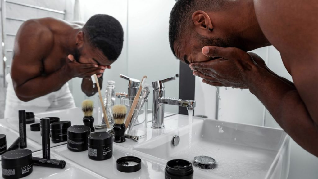 Man die gezicht wast in de wasbak, zij-aanzicht