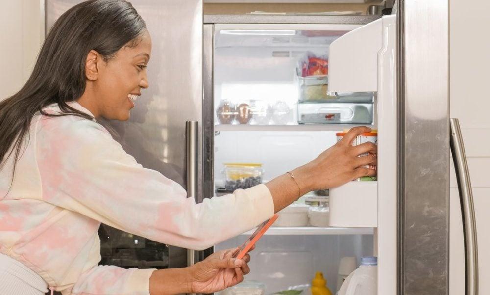 Vrouw opent koelkast en haalt etenswaren eruit. Vooraanzicht