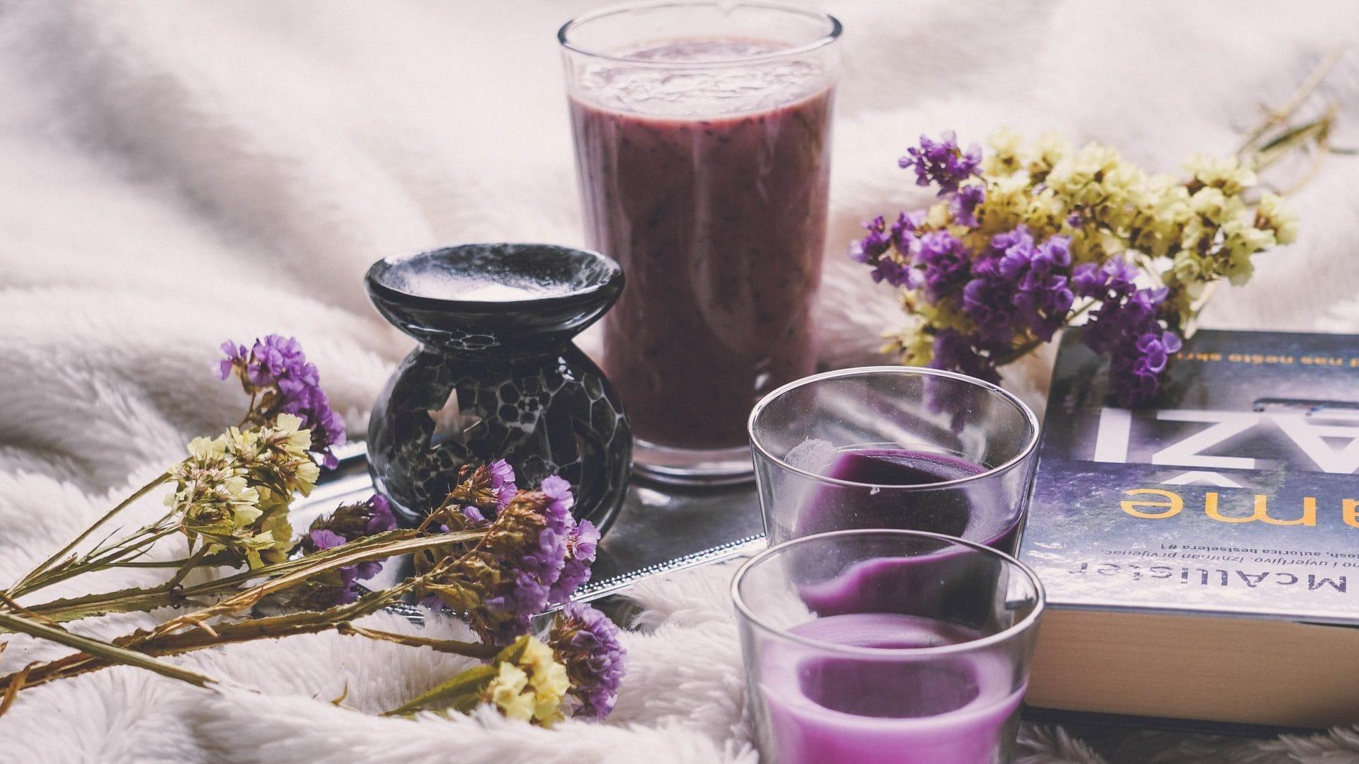 Lavendel  geurkaarsen, met boek en bloemen. Vooraanzicht.