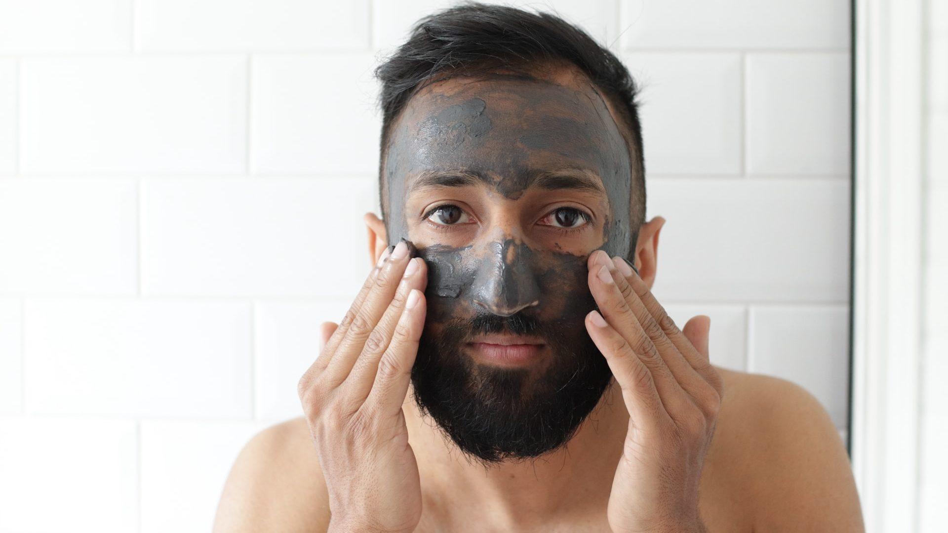 Man met baard en donker haar die masker aanbrengt