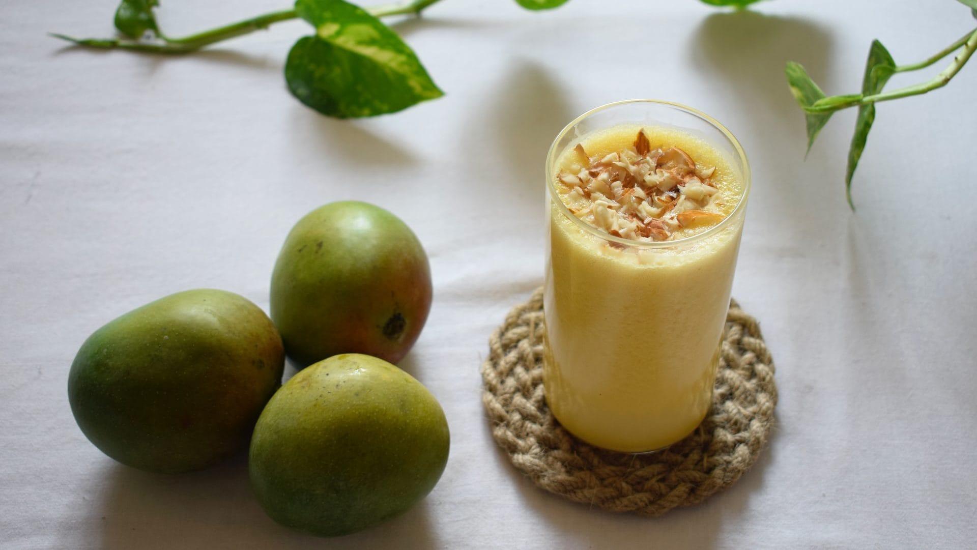 Fruitshake in glas met drie mango's ernaast.