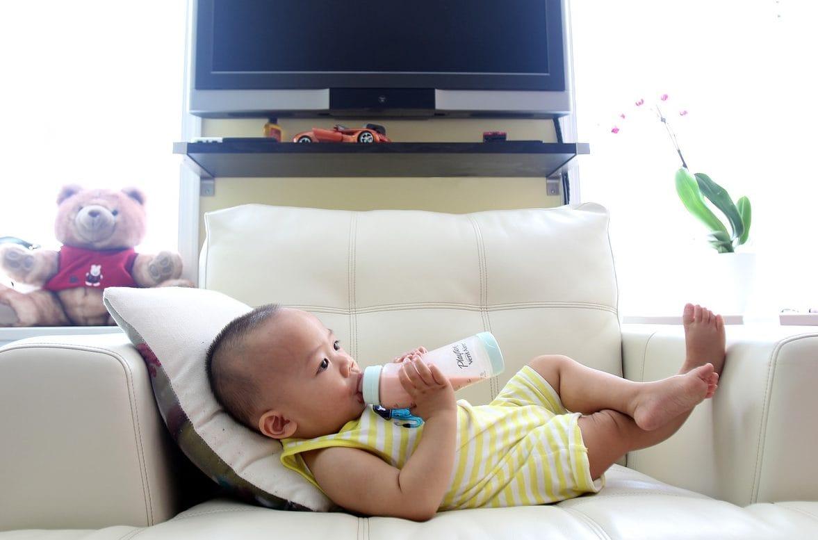 Kindje wat op de bank zijn flesje drinkt. zij-aanzicht