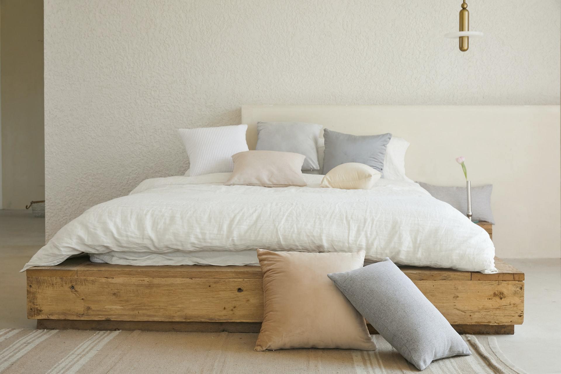 Houten bed met wit dekbed, vooraanzicht