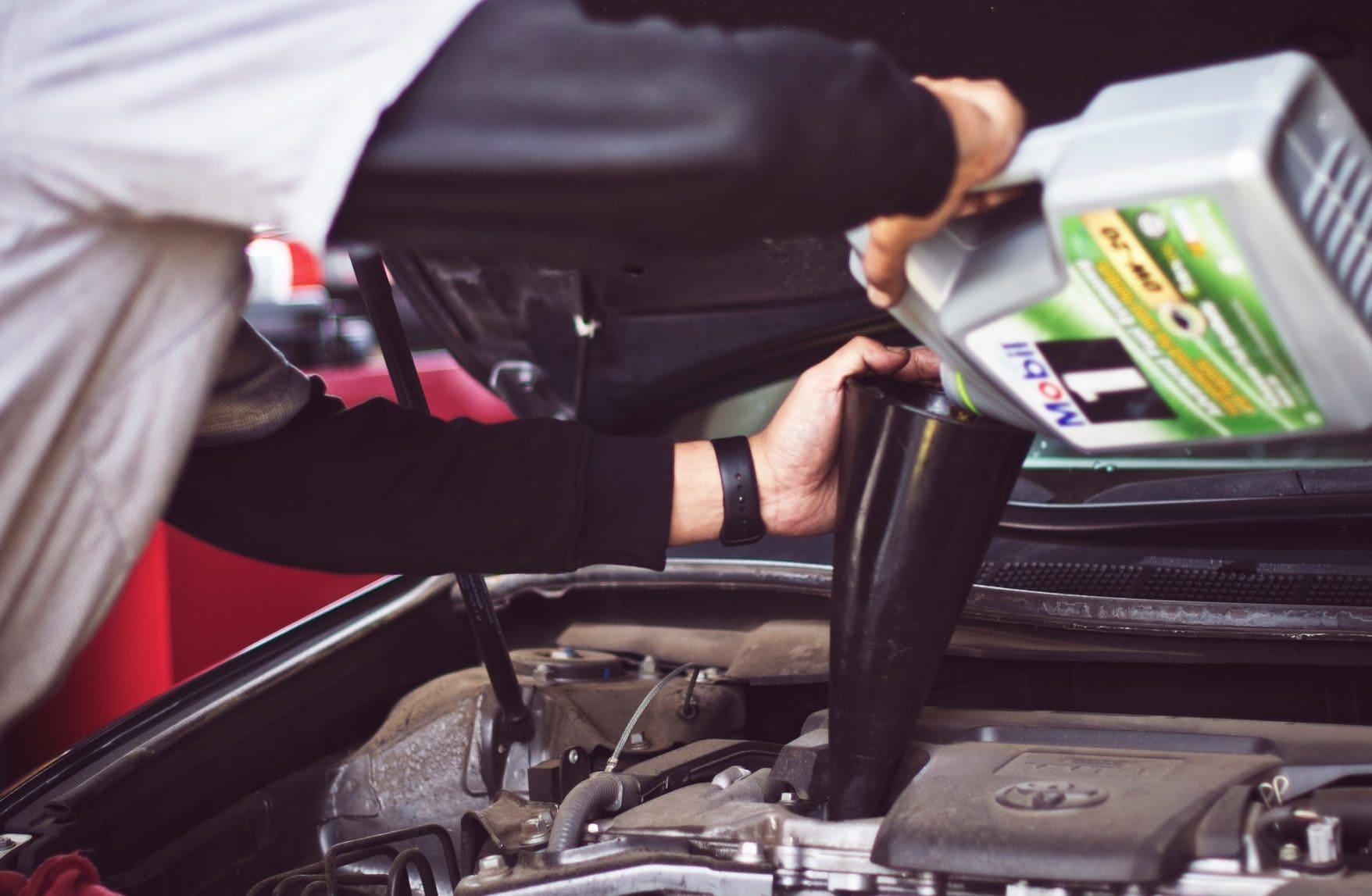 Iemand vult olie bij in auto