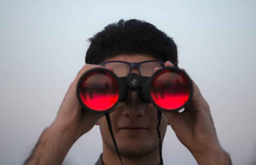 Persoon die door verrekijker heen kijkt, vooraanzicht