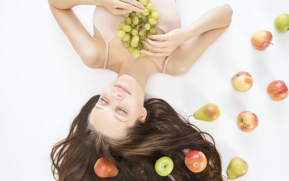 Vrouw met lang haar en fruit om zich heen, bovenaanzicht