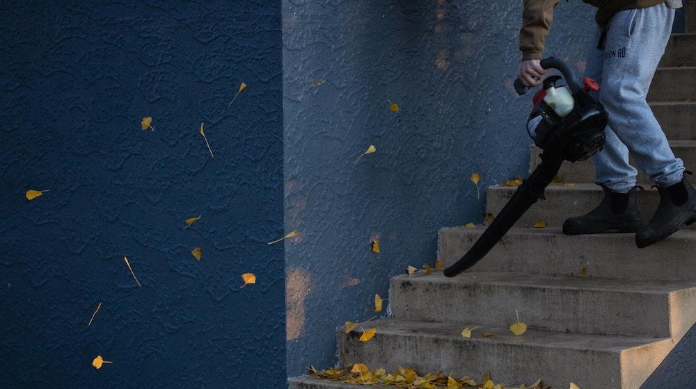 man met bladblazer op trap