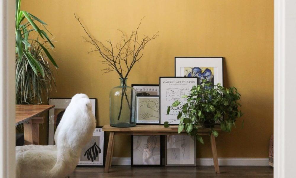 Gele muur met tafeltje en foto's ervoor, vooraanzicht