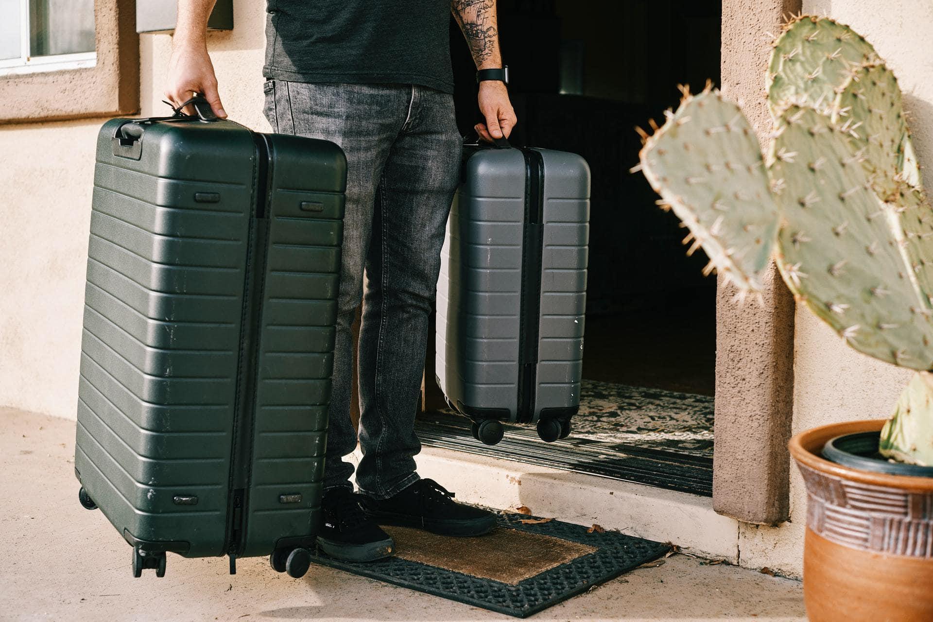 Persoon die twee koffers draagt