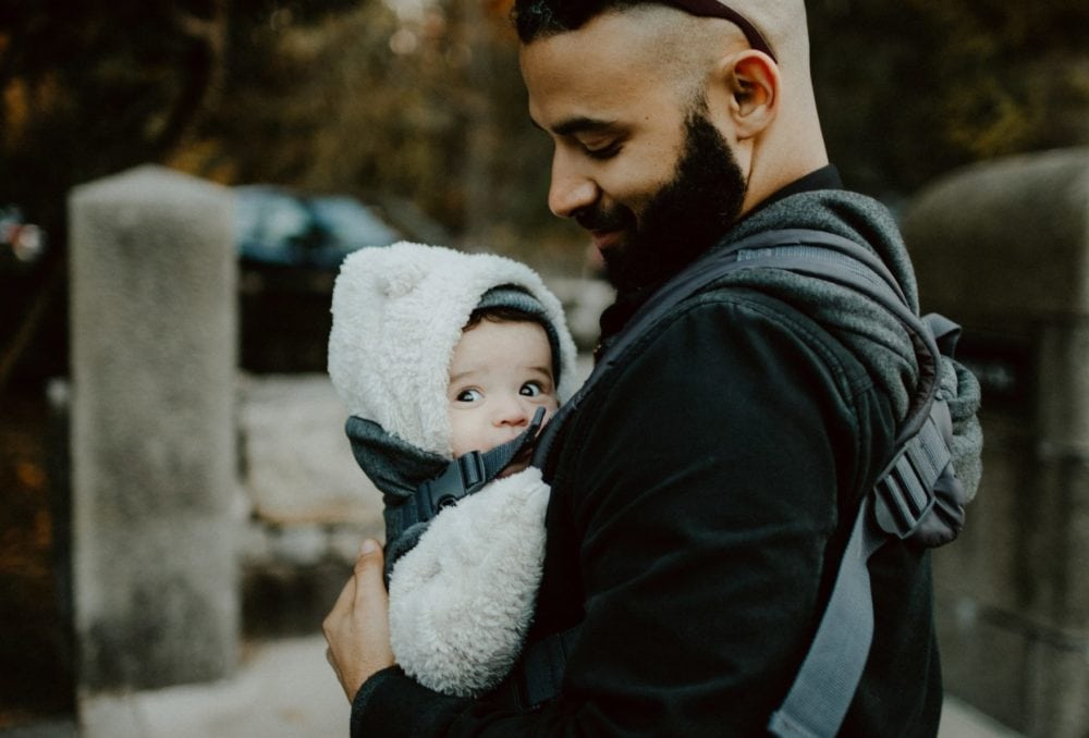 man met baby in draagzak, zij-aanzicht